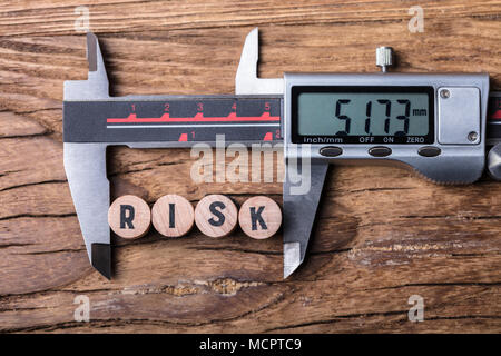 Elevated View Of Digital Electronic Vernier Caliper And Blocks With Risk Text On Wooden Background - Stock Photo