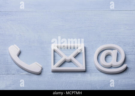 High Angle View Of White Phone, Email and Post Icons Isolated On Wooden Plank - Stock Photo