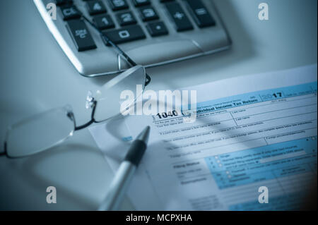 1040 US Tax form with calculator, pen and glasses - Stock Photo