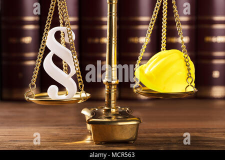 Close-up Of White Paragraph Symbol And Yellow Hard Hat On Justice Scale - Stock Photo