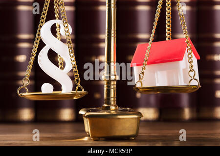 Close-up Of Paragraph Symbol And House Model On Golden Justice Scale - Stock Photo