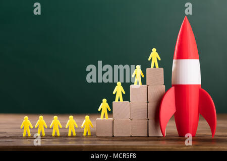 Close-up Of Rocket Besides Yellow Human Figures On Top Of Wooden Blocks In Classroom - Stock Photo