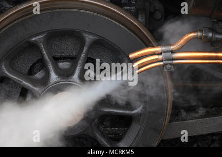 steam coming out of copper pipes on old locomotive engine - Stock Photo