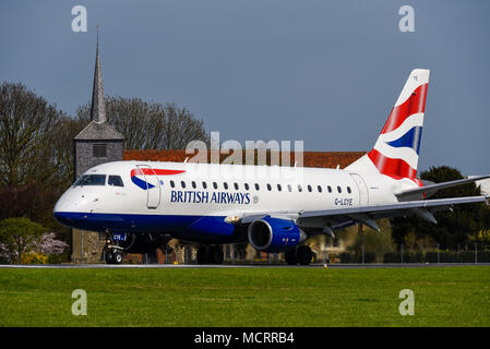 British Airways Embraer 170 ERJ170 G-LCYE carrying out training flights from London Southend Airport, Essex. BA Flight training. Taxiing past church - Stock Photo