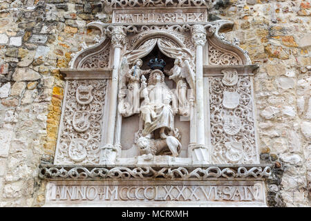 Bas relief of king of Hungary Matthias in full armour sitting with his feet on a lion. Angels hold a crown over his head. On both sides coat of arms.  - Stock Photo