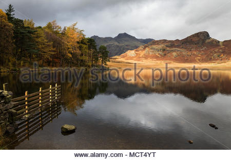Dramatic light on hills above Blea Tarn, Lake District, England with mountains reflected in still water of lake - Stock Photo