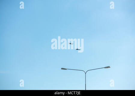 Military helicopters flying in the sky over a city and crowded event, taking photos, filming from above on clear blue sky background. An Isolated heli - Stock Photo