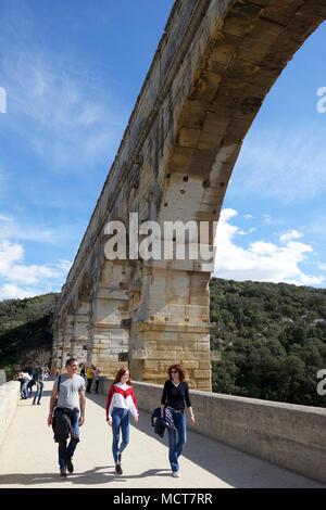 Tourists walking across the Pont du Gard Roman aqueduct near Nimes in France - Stock Photo