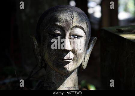 artistic, wooden Buddha head sculpture at a Buddhist temple Wat, Chiang Mai, Thailand - Stock Photo