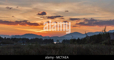 View over sunset of Liptovska Mara lake with shore of Liptovsky Trnovec village in Slovakia. Chocsky hills can be seen in the distance. Stock Photo