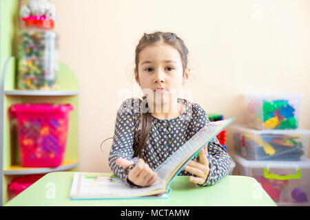 Cute little girl doing homework, reading a book, coloring pages, writing and painting. Children paint. Kids draw. Preschooler with books at home. Preschoolers learn to write and read. Creative toddler - Stock Photo