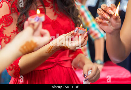 Hands and fingers are drawn to henna . Female hand with henna tattoo . . She holds the candle in his hand Henna party - Stock Photo