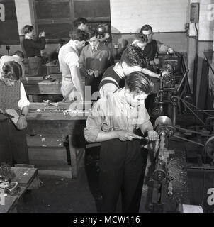 Historical picture, 1950s, of a group of male engineering apprentices using machine tools and getting 'hands on', practical experience in an industrial workshop, England, UK. In post-war Britain there was a major expansion of technical colleges and apprenticeship schemes to encourage more young people into important industrial sectors such as engineering and manufacturing. - Stock Photo