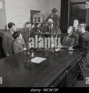 1950s, historical, Mining students in a college classroom being shown a model of a working coalmine by a male teacher, England, UK. in post-war Britain, mining was an important industry with over 500 pits in existence and the government of the day actively encouraged young people to learn mining skills and enter the industry. - Stock Photo