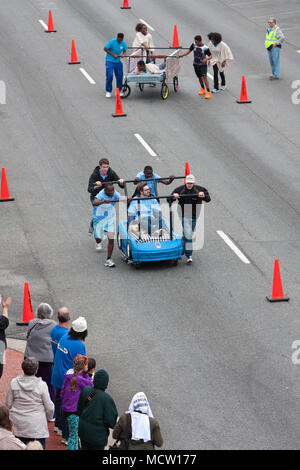 High-angle view of two teams pushing beds down city street in the annual Lawrenceville Bed Race, on March 29, 2014 in Lawrenceville, GA. - Stock Photo