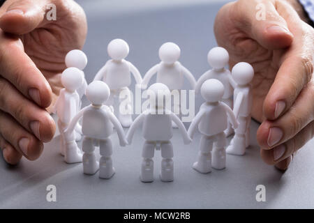 Close-up Of A Person's Hand Protecting Miniature Human Figures On Grey Background - Stock Photo