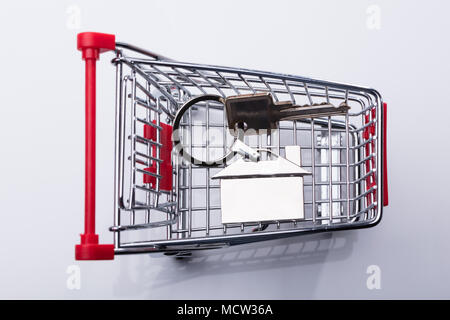 Elevated View Of Shopping Cart And House Key Isolated On White Background - Stock Photo