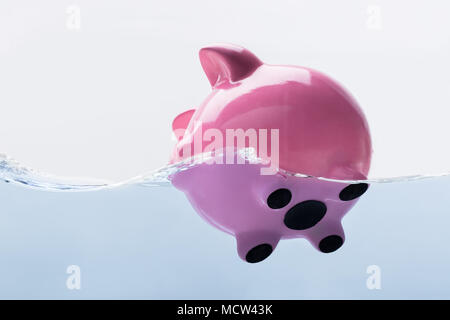 Close-up Of A Pink Piggy Bank Drowning In Water - Stock Photo