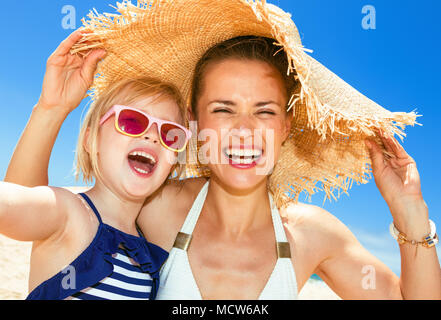 Family fun on white sand. happy modern mother and child in swimwear on the seacoast taking selfie - Stock Photo