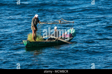 Two Egyptian local men in traditional dress and turbans in small rowing boat with fishing nets, early morning light, River Nile, Egypt, Africa - Stock Photo