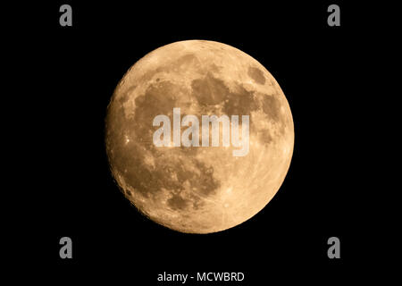 Closeup of a large shining full moon against dark background - Stock Photo