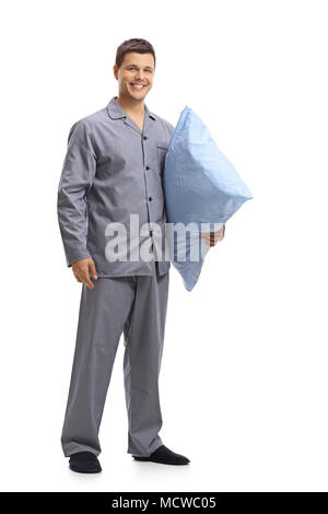Full length portrait of a young man in pajamas holding a pillow isolated on white background - Stock Photo