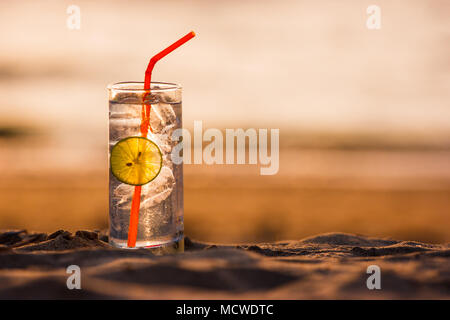 Picture of a glass of Gin Tonic with straw and lime slice on the beach, at sunset. Long Beach, Ko Lanta, Thailand. - Stock Photo