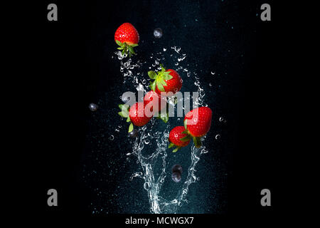 Fresh berries in splashes of water on black background. Juicy strawberries and blueberries. To stop a moment - Stock Photo