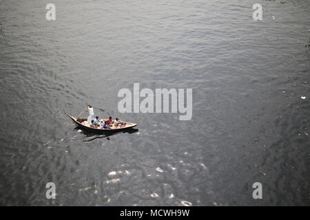 Dhaka, Bangladesh. Bangladeshi residents cross polluted Buriganga River by small wooden boat in Dhaka, Bangladesh on April 17, 2018. Thousands people cross the Buriganga river everyday, which is becoming deadly river as the chemical waste of mills and factories, household waste eventually makes its way into the Buriganga River. © Rehman Asad/Alamy Stock Photo - Stock Photo