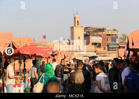 Salesmen trying to catch attention of the passing crowd of people at the food market stalls at the famous Jemaa el-Fnaa square in Marrakesh, Morocco - Stock Photo