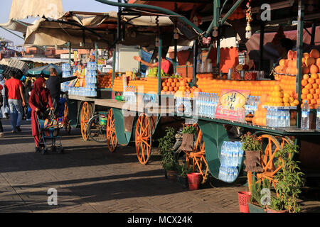 Salesmen trying to sell freshly squeezed orange juice on the market at the famous Jemaa el-Fnaa square in Marrakesh, Morocco - Stock Photo