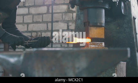 Man blacksmith forges the metal at the mechanical hammer - Stock Photo