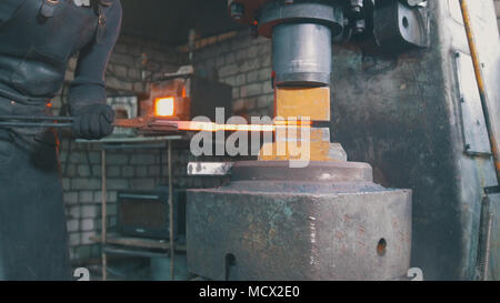 Automatic hammering - blacksmith forging red hot iron on anvil, extreme close-up - Stock Photo