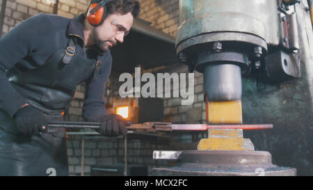 Blacksmith forging red hot iron on anvil - automatic hammering - Stock Photo