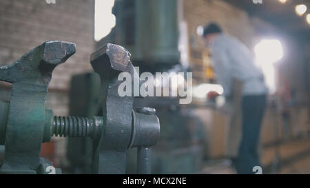 Blacksmith forging red hot iron on anvil - automatic hammering, de-focused - Stock Photo