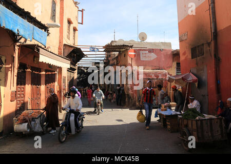 People walking through the streets of the old Medina Quarter in front of the entrance to the traditional Souk - Marrakesh, Morocco - Stock Photo