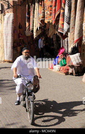 Muslim man in traditional clothing and fancy sunglasses on motorbike passing by a market stall selling carpets and other textil in Marrakesh, Morocco - Stock Photo