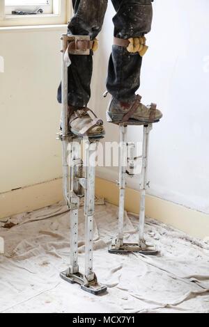 Plasterer on stilts plastering a high ceiling - Stock Photo