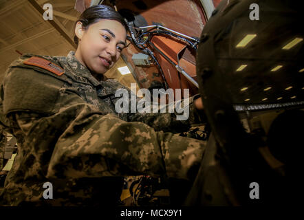 U.S. Army National Guard Private 1st Class Katherine Silva works on a UH-60L Black Hawk helicopter in the New Jersey National Guard's Army Aviation Support Facility, Joint Base McGuire-Dix-Lakehurst, N.J., March 5, 2018. Silva is an avionics mechanic with the 1st Assault Helicopter Battalion, 150th Aviation Regiment, and spends her spare time collecting and creating comics that feature strong female characters. (U.S. Air National Guard photo by Master Sgt. Matt Hecht) - Stock Photo