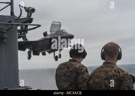 180305-N-JN784-242 EAST CHINA SEA (March 5, 2018) Marines observe as an F-35B Lightening II with Marine Fighter Attack Squadron (VMFA) 121 flies above the amphibious assault ship USS Wasp (LHD 1), marking the first time the aircraft has deployed aboard a U.S. Navy ship and with a Marine Expeditionary Unit in the Indo-Pacific. VMFA-121, assigned under the Okinawa-based 31st Marine Expeditionary Unit, will remain embarked aboard Wasp for a regional patrol meant to strengthen regional alliances, provide rapid-response capability, and advance the Up-Gunned ESG concept. (U.S. Navy photo by Mass Com Stock Photo