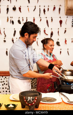 Chef José Luis Diaz and his mother cooking enchiladas de san pedro totolapam (meat-filled tortillas with chile sauce) with him  Restaurante Chilhuacle - Stock Photo