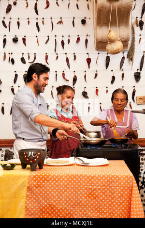 Grandmother, and mother of Chef José Luis Diaz cooking enchiladas de san pedro totolapam (meat-filled tortillas with chile sauce) with him  Restaurant - Stock Photo