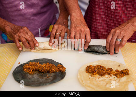 Grandmother, and mother of Chef José Luis Diaz cooking enchiladas de san pedro totolapam (meat-filled tortillas with chile sauce)  Restaurante Chilhua - Stock Photo