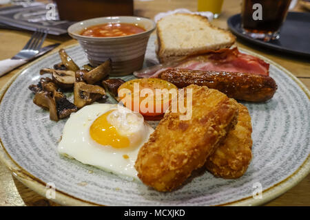 A view of a full English breakfast at a cafe with fried egg, sausage, bacon, fried mushrooms, hasb browns and baked beans. - Stock Photo