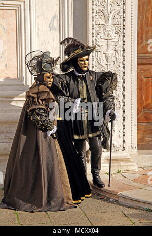 Disguised couple with Venetian masks, carnival in Venice, Italy - Stock Photo