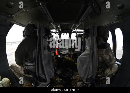 N.Y. Army National Guard Soldiers with 3rd Battalion, 142nd Aviation, sit in a UH-60 Black Hawk Helicopter, at the Army Aviation Facility 3, Latham, N.Y., March 3rd, 2018. The 3-142nd was conducting air assault training. (N.Y. National Guard photo by Spc. Andrew Valenza) - Stock Photo