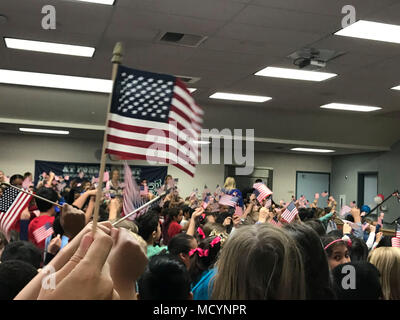 Students and staff members at Bonsall West Elementary School wave flags as they sing along with 'Proud to be an American' by Lee Greenwood during a depute for 'Project AIM High' (academic achievement, innovation, mental health) March 7, 2018. Bonsall West received a grant from the Department of Defense Education Activity that will allow the school to improve learning through STEM (science, technology, engineering and math) programs.(U.S. Marine Corps photo by Lance Cpl. Brooke Woods) - Stock Photo