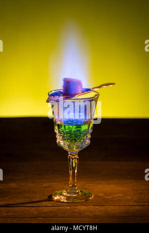 Burning sugar on spoon in glass of absinthe. - Stock Photo