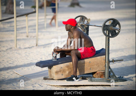 MIAMI - DECEMBER 27, 2017: Muscular young man works out at the outdoor workout station in Lummus Park known as Muscle Beach. - Stock Photo