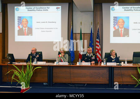 A video statement by Ambassador Lewis M. Eisenberg, United States Ambassador to the Italian Republic, plays on a projector screen for attendees during the opening ceremony of the 8th Gender Protection in Peace Operations Course at the Center of Excellence for Stability Police Units (CoESPU) in Vicenza, Italy, Mar. 8, 2018. The event brought together military and civic leaders from the local community to celebrate International Women's Day. (U.S. Army Photo by Paolo Bovo) - Stock Photo